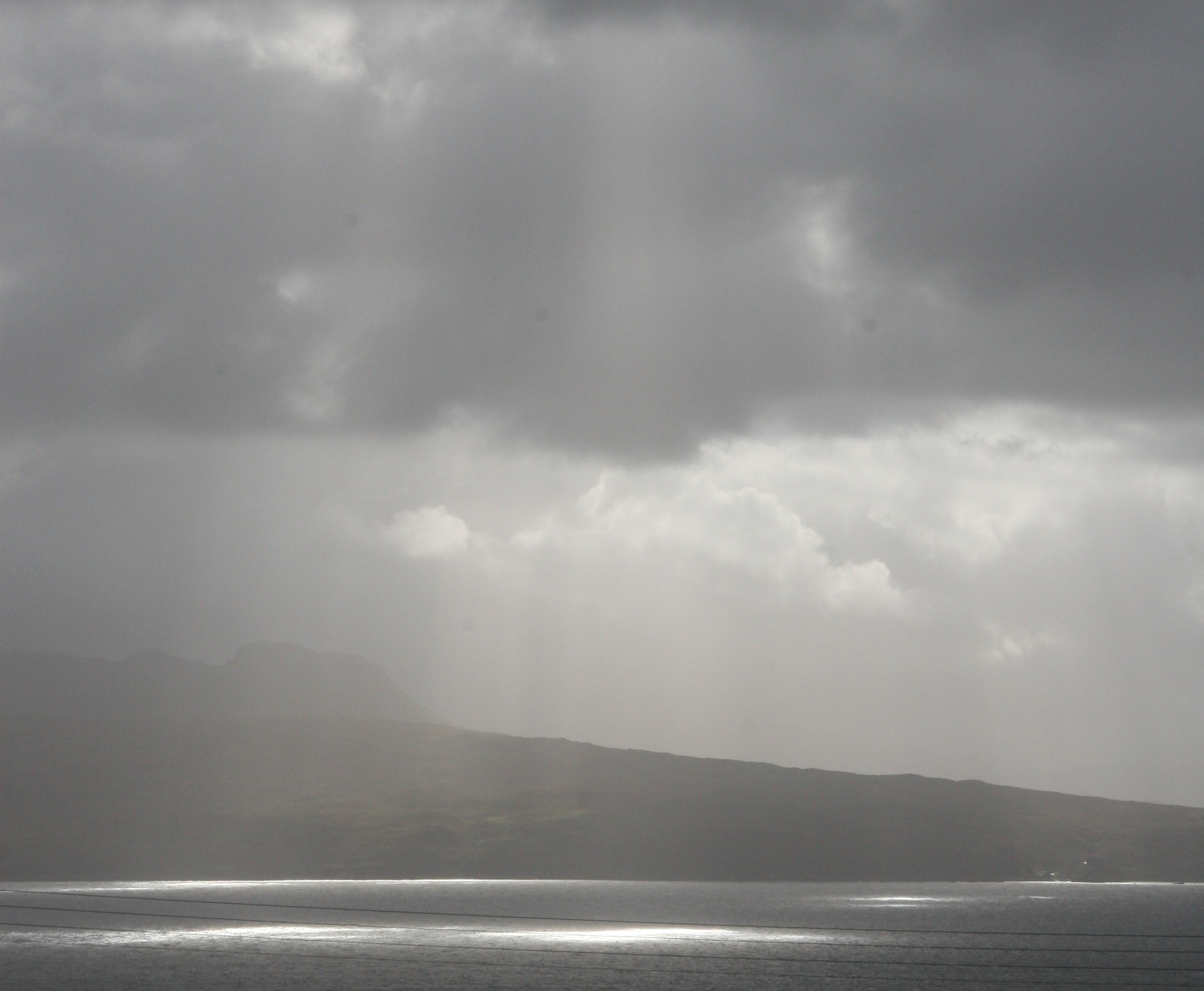 Rays of light piercing through the cloud reflecting off the Sound of Slet, Isle of Skye, Skye White House